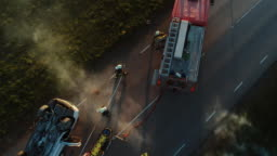 Aerial View: Rescue Team of Firefighters and Paramedics Work on a Car Crash Traffic Accident Scene. Preparing Equipment, First Aid Help. Saving Injured and Trapped People from the Burning Vehicle