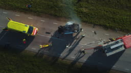 Aerial View: Rescue Team of Firefighters and Paramedics Work on a Car Crash Traffic Accident Scene. Preparing Equipment, First Aid Help. Saving Injured and Trapped People from the Vehicle. Zoom in
