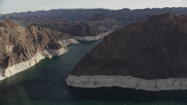 vídeos de stock, filmes e b-roll de aerial view revealing the hoover dam behind mountains - represa hoover