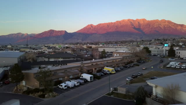 vídeos de stock e filmes b-roll de aerial view rising above building to view mountain lit up by the sun - orem