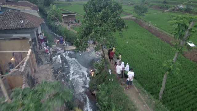 aerial view rising from a polluted section of the river citarum to people walking beside a field, indonesia. - textile industry stock videos & royalty-free footage