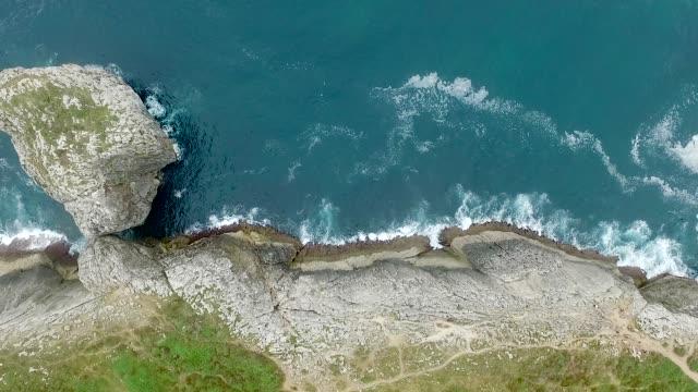 vídeos de stock e filmes b-roll de aerial view rock cliffs on a coastline - penhasco caraterísticas do território