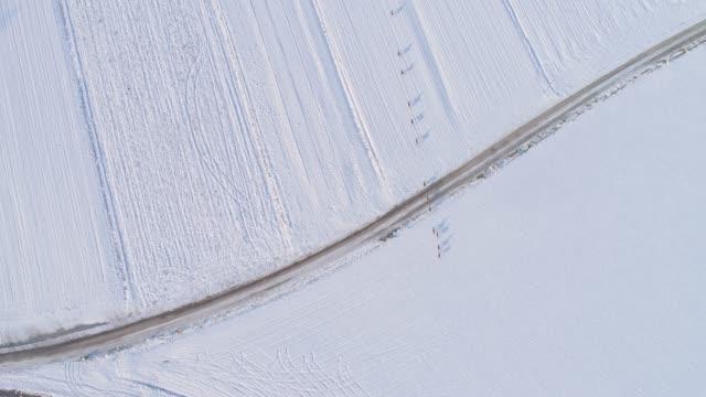 El ROE de la vista aérea de WS corriendo a través del campo rural cubierto de nieve