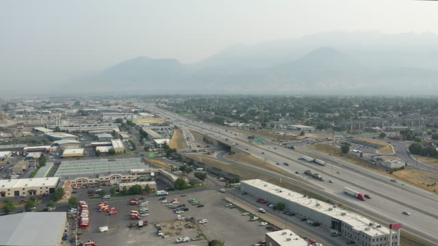 aerial view rotating over industrial area next to freeway with smokey skies - orem utah stock videos & royalty-free footage