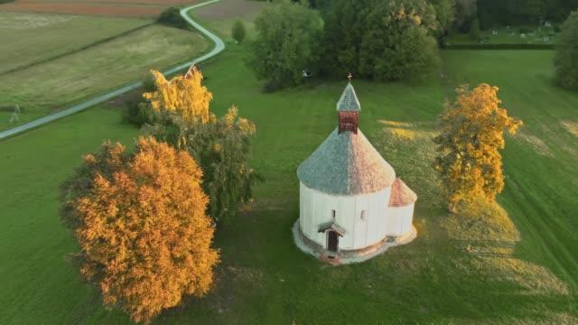 ms aerial view round church in tranquil,idyllic rural landscape,prekmurje,slovenia - prekmurje stock videos & royalty-free footage