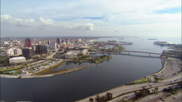 aerial view shipping container facility over water towards waterfront area / over bridge towards marina / long beach, california - long beach california video stock e b–roll