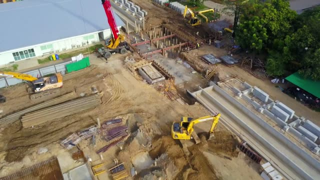 aerial view shot of combine cycle power plant construction site with tower crane, mobile crane, backhoe, excavator and steel structure of boiler and cooling tower near river - earth mover stock videos & royalty-free footage