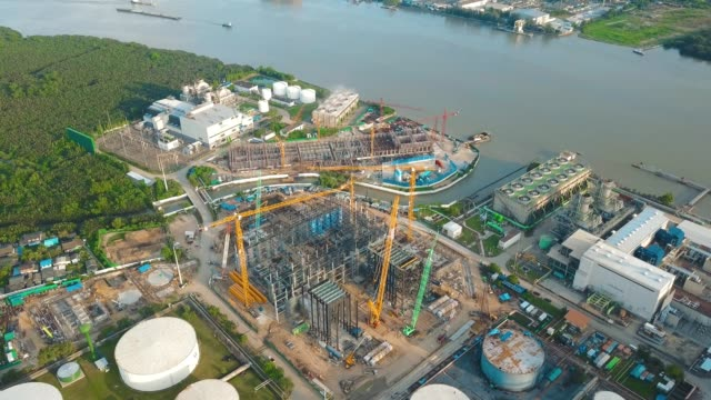 aerial view shot of combine cycle power plant construction site with tower crane, mobile crane and steel structure of boiler and cooling tower near river - crane stock videos & royalty-free footage