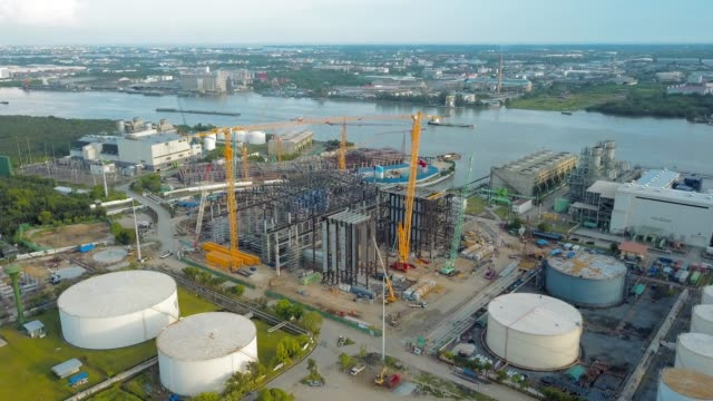Aerial View shot of Combine cycle power plant Construction Site with tower crane, Mobile crane and steel structure of boiler and cooling tower near river