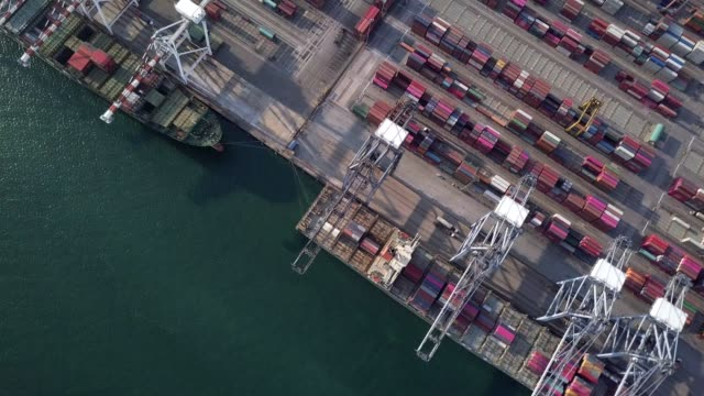 4k aerial view shot of commercial port export and import goods and thousands of containers in harbor - crane construction machinery stock videos & royalty-free footage