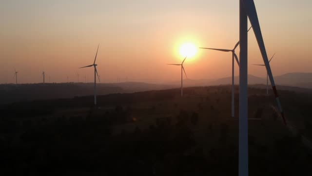 aerial view shot of wind turbines at sunset - alternative energy stock videos and b-roll footage