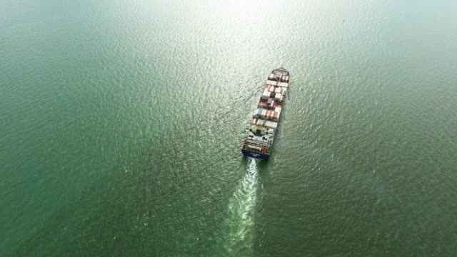aerial view shot track of cargo's container ship yard in ocean. - cargo ship stock videos & royalty-free footage