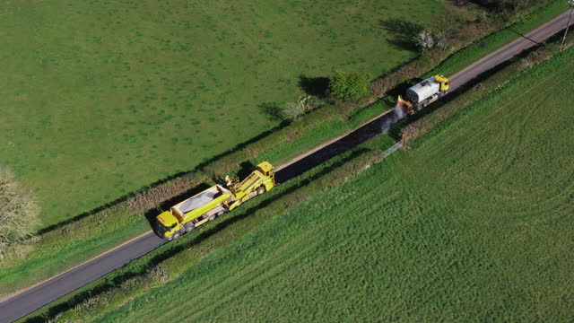 aerial view showing road workers laying fresh asphalt on a country road, england, united kingdom - construction vehicle stock videos & royalty-free footage