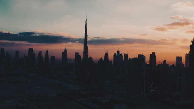 aerial view showing skyscrapers at sunrise, dubai, united arab emirates - 逆光点の映像素材/bロール