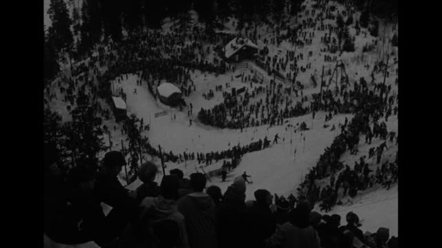 vídeos de stock e filmes b-roll de aerial view ski slope at 1952 oslo winter olympics / crowds watch as one person skis down the slalom / cu american andrea mead lawrence in goggles... - roupa de esqui