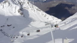 Aerial view skiers and snowboarders on ski lift on snow mountain in ski resort. Ski elevator for people transportation in mountain resort drone view. Winter sport on ski resort