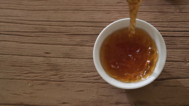 aerial view slow motion steep tea in to the cup - steep stock videos & royalty-free footage