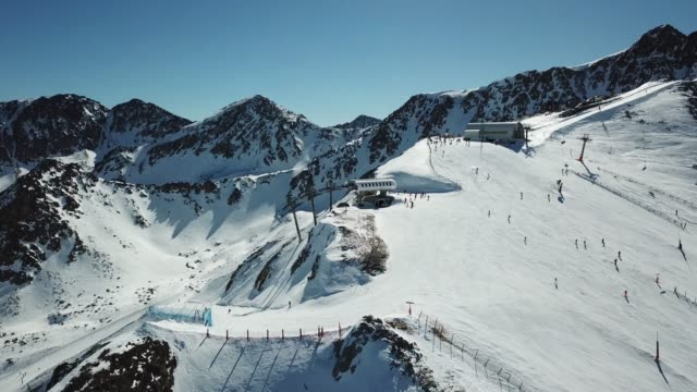 aerial view smooth movement along the ski slopes in the ski resort of grandvalira in andorra. magnificent snowy mountains and blue sky. winter landscape - image stock-videos und b-roll-filmmaterial