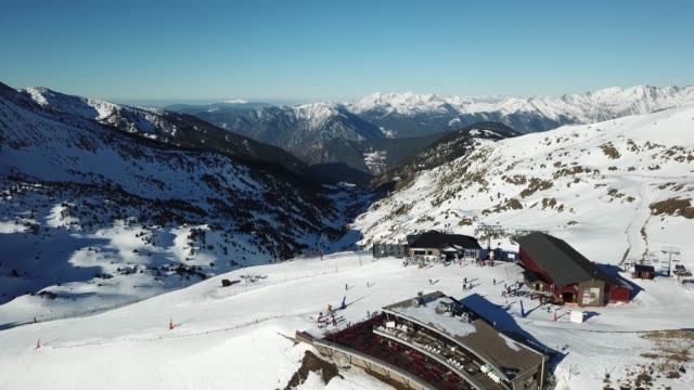 aerial view smooth movement along the ski slopes in the ski resort of grandvalira in andorra. magnificent snowy mountains and blue sky. winter landscape - light blue stock videos & royalty-free footage