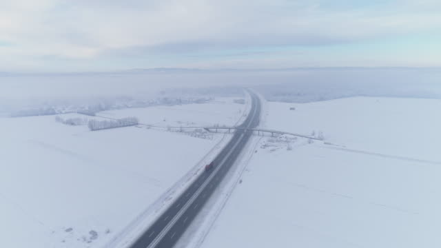 ws aerial view snow covered fields surrounding freeway - truck stock videos and b-roll footage