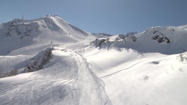 vídeos y material grabado en eventos de stock de aerial view snowcovered mountain ski slope in roza khutor ski resport / aerial view of skiers on ski slope and caucasus mountain range aerials roza... - sochi