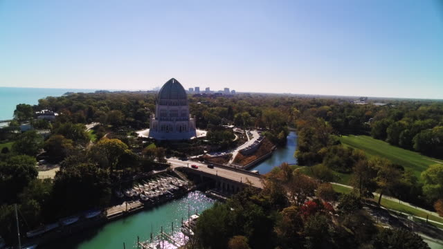 Aerial view soaring past Bahá'í House of Worship and marina on a clear blue sky in the Fall, Illinois