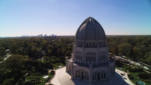 Aerial view soaring past Bahá'í House of Worship and marina on a clear blue sky in the Fall