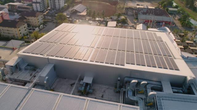 stockvideo's en b-roll-footage met aerial view solar power dak bij zonsondergang - industriëel gebouw