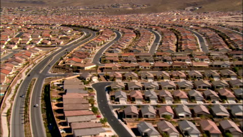 vidéos et rushes de aerial view streets running through rows of tract housing with hills in background / las vegas, nevada - lotissement