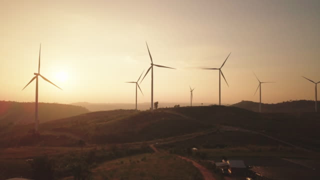 vídeos y material grabado en eventos de stock de salida del sol de vista aérea de las turbinas eólicas, 4k dci - imagen virada