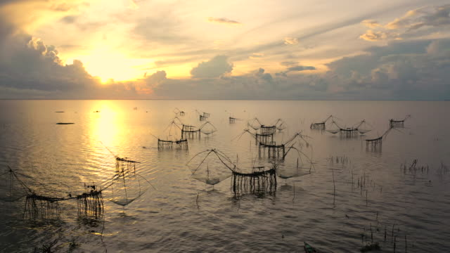 aerial view sunrise scene at the fisherman village with silhouette of wooden fishing net and long tail wooden boat , pakpra, pattalung, thailand - bamboo shoot stock videos & royalty-free footage