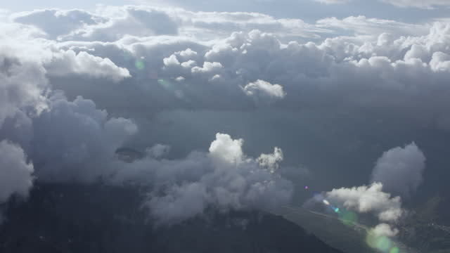 aerial view surrounded by large fluffy clouds far above the swiss alps. - majestic stock videos & royalty-free footage