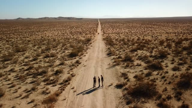 aerial view: three men standing on dirt track in desert landscape - joshua tree national park stock videos & royalty-free footage