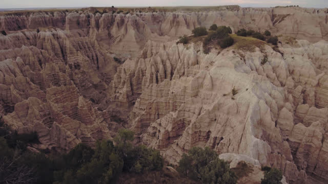 drone. aerial view tilting down to prehistoric badlands canyons speckled with vegetation during the day - badlands national park video stock e b–roll