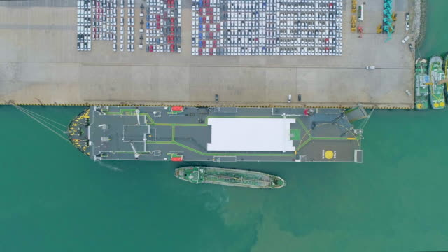 aerial view time lapse : aerial view large roro (roll on/off) car or vehicle carrier vessel convoy car and truck into and out of the worldwide market. - convoy stock videos and b-roll footage
