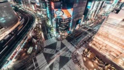4K UHD Aerial view time-lapse of Ginza road intersection at night, crowded people walking on zebra crossing and car traffic light trails. Asia transportation, Asian city life, or Japan tourism concept