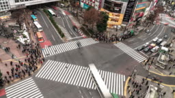4K UHD Aerial view time-lapse of Shibuya zebra crossing with crowded people and car traffic transport across intersection. Tokyo tourist attraction landmark, Japan tourism, or Asian city life concept