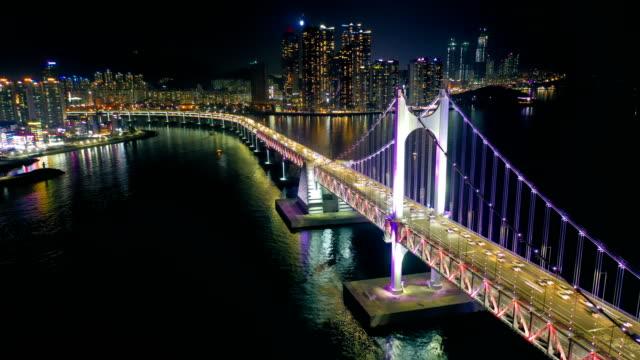 aerial view timelapse/hyperlapse of gwangan bridge with busan city at night - busan stock videos & royalty-free footage