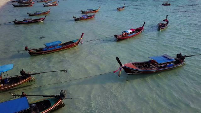 aerial view tracking long tail boat and rocky coast with crystal clear turquoise water koh lipe, satun, thailand - longtail boat stock videos & royalty-free footage