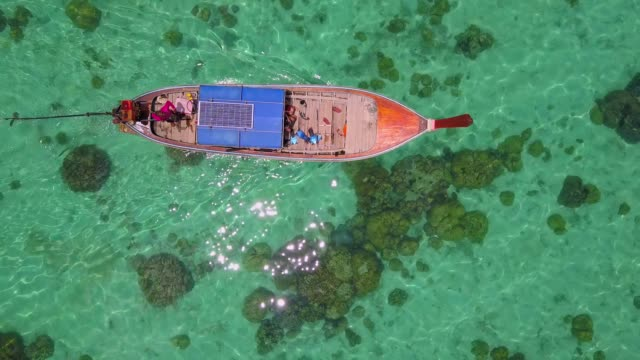 aerial view tracking of asian woman in bikini, long tail boat and rocky coast with crystal clear turquoise water koh lipe, satun, thailand - barca a motore video stock e b–roll