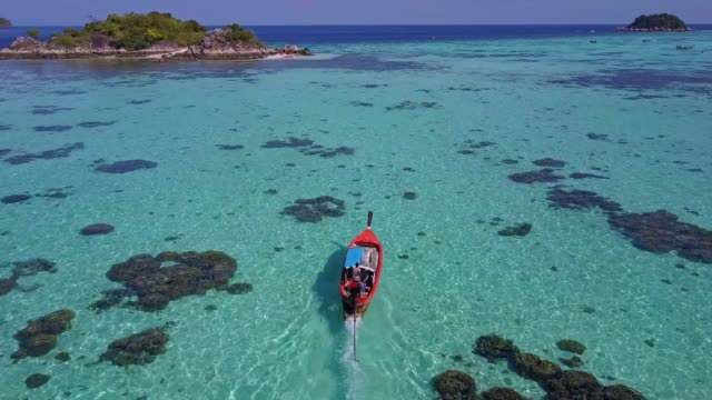 aerial view tracking of asian woman in bikini, long tail boat and rocky coast with crystal clear turquoise water koh lipe, satun, thailand - pattaya stock videos & royalty-free footage