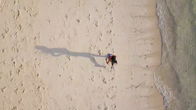 Aerial view tracking shot of Sports jogger Asian woman running on beach in island