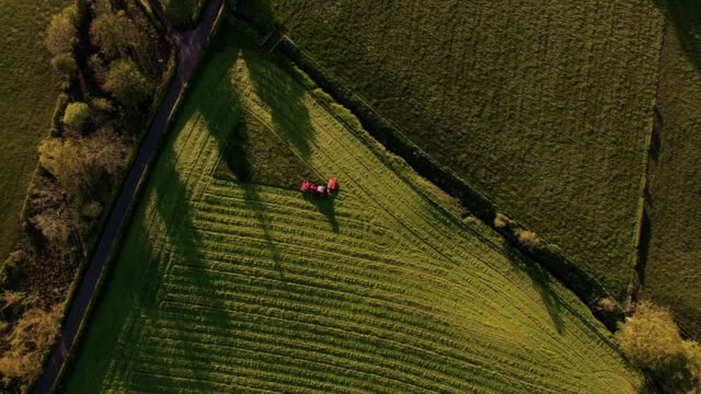 aerial view tractor finishing mowing field - scotland stock videos & royalty-free footage