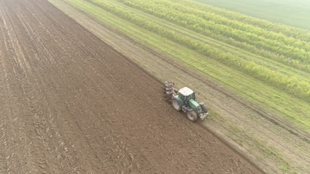 ms aerial view tractor plowing rural field,slovenia - zoom out stock videos & royalty-free footage