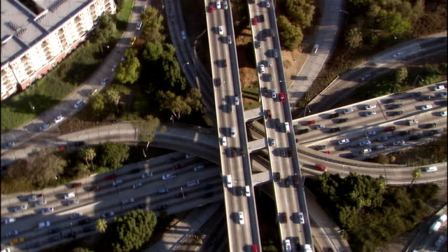 Aerial view traffic on highway interchange / tilt up downtown cityscape / Los Angeles, California
