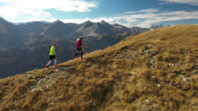 4K aerial view trail running couple in mountains