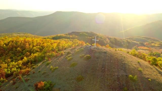 luftaufnahme ruhige, idyllische, hügelige herbstlandschaft mit christlichem kreuz auf einem hügel stock video - weichzeichner stock-videos und b-roll-filmmaterial