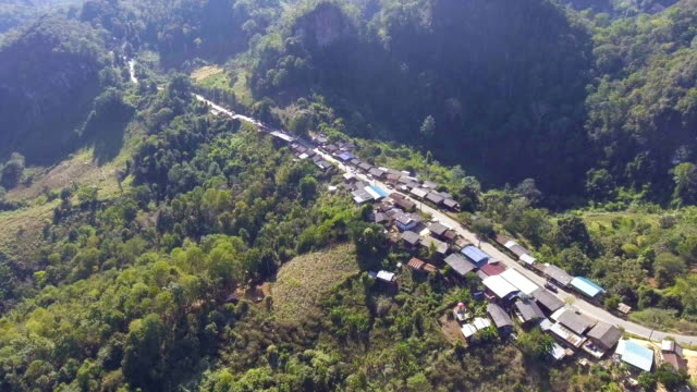 Aerial view : Tranquil small tribe village on the mountain with morning sunlight