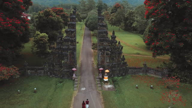 aerial view  traveler couple running at the gates hindu temple bali, indonesia - indonesia travel stock videos & royalty-free footage