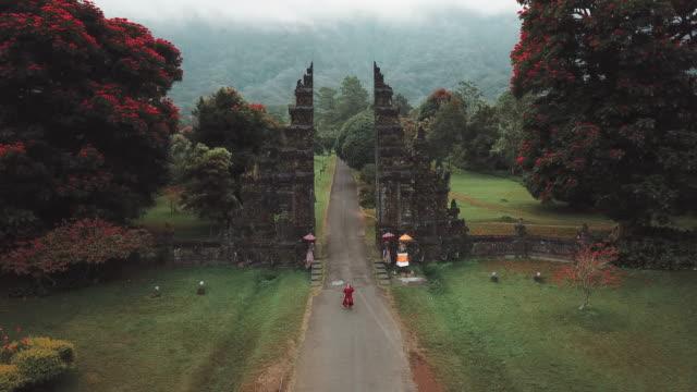 vidéos et rushes de femme de voyageur de vue aérienne fonctionnant au temple hindou de portes bali, indonésie - chaîne de montagnes